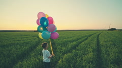 Boy running across the field with a balloon. RAW video record Stock Footage