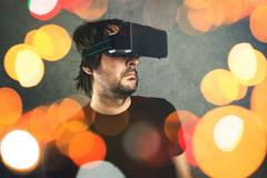 Man with virtual reality goggles enjoying 3d VR multimedia content Stock Photos