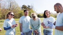 Group of volunteers listening to mentor in park Stock Footage