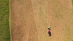 Aerial shot a high clip as a farmer cuts and bails hay with a tractor Stock Footage