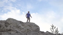 Slow motion. Man climbs on top of the mountain. Running over rough terrain. Stock Footage