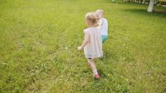 Kids running across green grass - stock footage