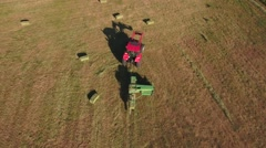 Aerial shot as a the tractor cuts and bails hay Stock Footage