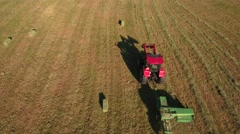 Aerial shot as a tractor cuts and bails hay Stock Footage