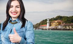 Woman with thumbs up on the beach baclground. Stock Photos