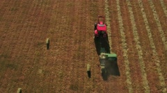 Aerial shot as farmer cuts and bails hay Stock Footage