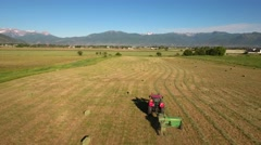 Aerial shot as tractor cuts and bails hay Stock Footage
