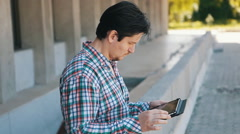 businessman in a plaid shirt uses the tablet outdoor - stock footage