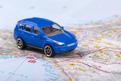 Road trip, small toy car on map Stock Photos