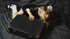 Pretty blond girl looks in an old suitcase - stock footage