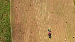 Aerial timelapse shot high clip as farmer cuts and bails hay Stock Footage