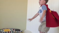 Slow motion a toddler with a cape jumps off his bed in room Arkistovideo