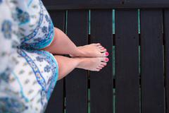 Bare feet girls on wooden bridge view from above - stock photo