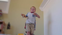 Slow motion toddler with a cape jumps on his bed Arkistovideo