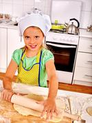 Child cooking dough at kitchen. - stock photo