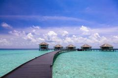 The path to the bungalow and island over the water - stock photo