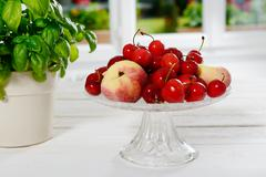 Cherries and peaches in a glass cup Stock Photos