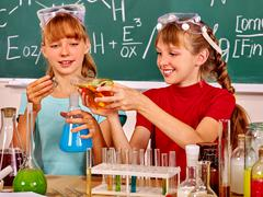 Children holding flask in chemistry class. - stock photo