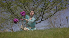Chinese Ribbon Dancer outdoor seated warm up traditional costume tracking shot Stock Footage