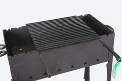 pattern of new metal brazier with grill for barbecue closeup - stock photo