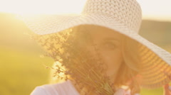 Girl in a straw hat and with flowers at sunset Stock Footage