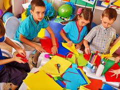 Kids working with paper on table in kindergarten . - stock photo