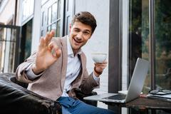 Man showing ok sign and using laptop in outdoor cafe - stock photo