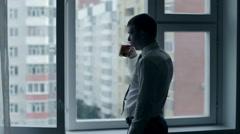 Groom in shirt drinks tea in front of the window Stock Footage
