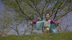 Chinese Ribbon Dancer outdoor seated warm up in traditional costume 1 Stock Footage