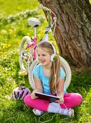 Bicycle girl wearing helmet watching at tablet pc in cycling. - stock photo