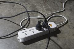 High angle view of cables connected to electric plug on floor - stock photo