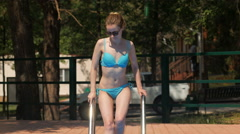 Blonde dressed in blue swimsuit is going down to the pool and swimming Stock Footage