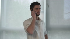 Young man standing near the window using app on mobile phone - stock footage