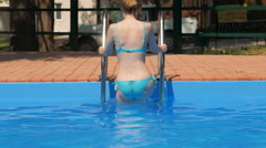 Blonde dressed in blue swimsuit is going out from a pool Stock Footage