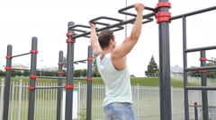 Sports lifestyle, street workout. Muscular man pulls on the bar. Stock Footage