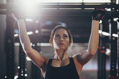 Close-up of young woman doing chin-ups at gym - stock photo