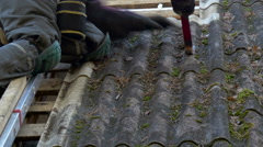 A worker removing the old roof sheets Stock Footage