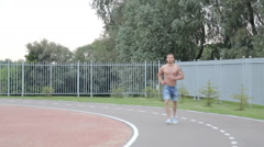 Man jogging in on dirt track Stock Footage