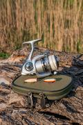 Fishing reel and various kind of baits on the natural background. Stock Photos