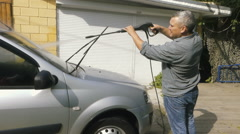 Man washing his silver car near the house. Stock Footage