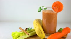 Orange smoothy in a glass. Banana, carrot, parsley and celery. 4K dolly video Stock Footage