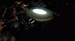 Brightly illuminated sports stadium during night city flyover, amazing cityscape Stock Footage