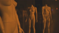 Naked stripped mannequins without clothes in hall of shop behing glass frontage Stock Footage