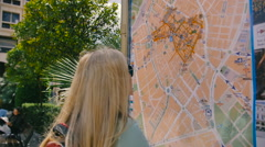 Tourist woman in sunglasses and backpack looking at the map stand - stock footage