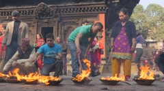 Devotees poking ritual fire at hindu temple,Patan,Nepal - stock footage
