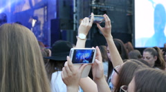 Young fan shooting video of concert performance via smart phone staying in crowd Stock Footage