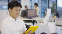 4K Businessman using tablet computer in office, coworker brings over document Stock Footage