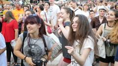 Teenage girls spectators cheerfully dancing in people crowd enjoying concert Stock Footage