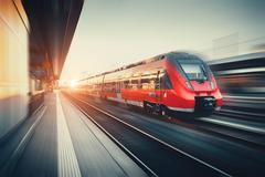 Beautiful railway station with modern red commuter train at sunset Stock Photos