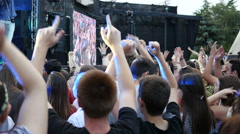 People crowd fans raising swaying clapping hands in front of stage music concert - stock footage